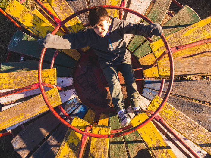 Directly above shot of boy sitting on merry go round at playground