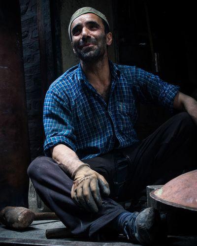 Happy Worker Sitting In Workshop