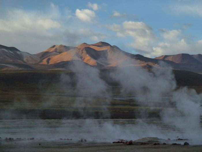 Geyser emitting from volcanic mountain against sky