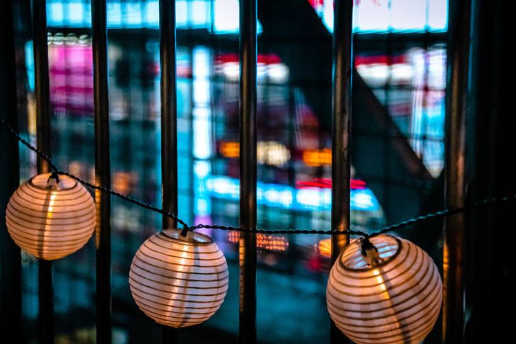 Close-up of illuminated lanterns hanging on glass window