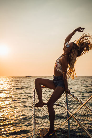 Water Sea One Person Sky Real People Beauty In Nature Lifestyles Sunset Horizon Leisure Activity Young Adult Horizon Over Water Full Length Scenics - Nature Women Nature Young Women Long Hair Hairstyle Hair Sun Outdoors Human Arm Arms Raised