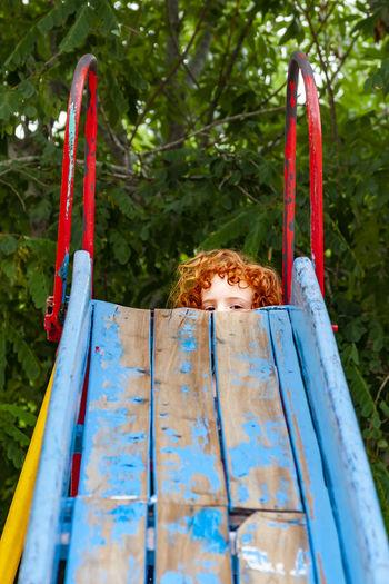 Portrait of girl on slide against plants