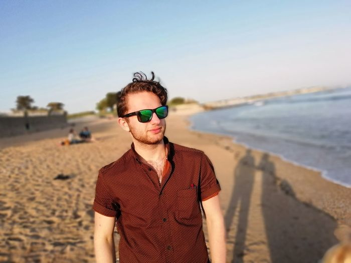 Young man wearing sunglasses standing on beach