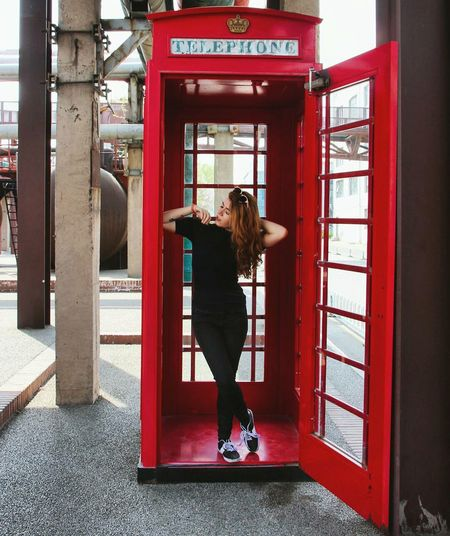 Young woman standing in telephone booth