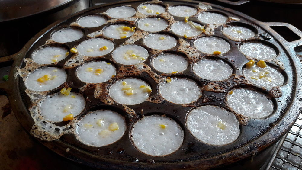 Thai Coconut Pudding cooked in a pan over a charcoal fire - Khanom Khrok in Thai Rice Flour Pudding Street Food Coconut Milk Ready To Eat Cooking Thailand Traditional Sweet Dessert Food And Drink No People Indoors  Close-up Freshness Food Day Ready-to-eat