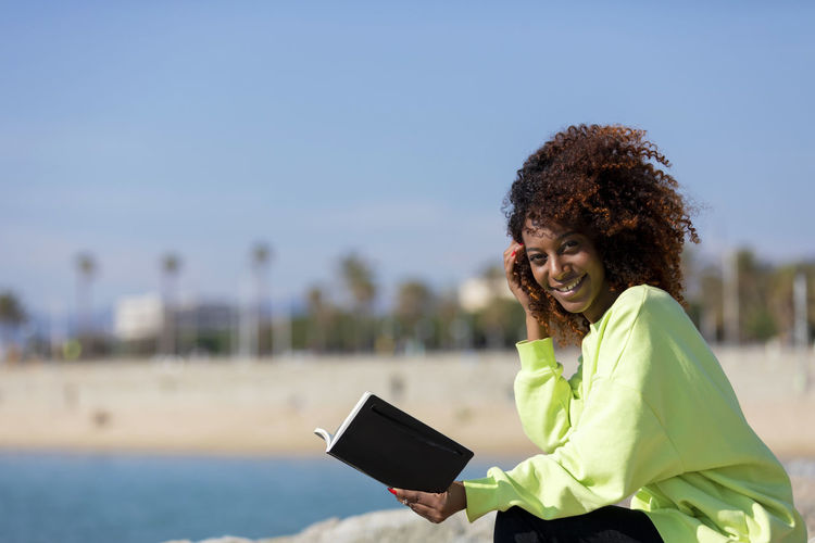 Side view of young curly afro woman sitting on a breakwater holding a book while smiling and looking camera outdoors Wireless Technology Smiling Technology Curly Hair Communication One Person Focus On Foreground Happiness Connection Mobile Phone Young Adult Hairstyle Women Hair Real People Portrait Day Leisure Activity Standing Waist Up Outdoors Woman African American Afro Denim Happiness Happy Fun Daylight Sunlight