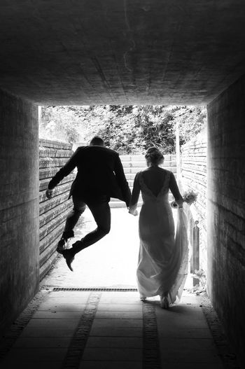 Rear view of couple standing against wall