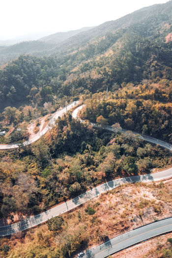 Aerial view of road amidst trees against sky