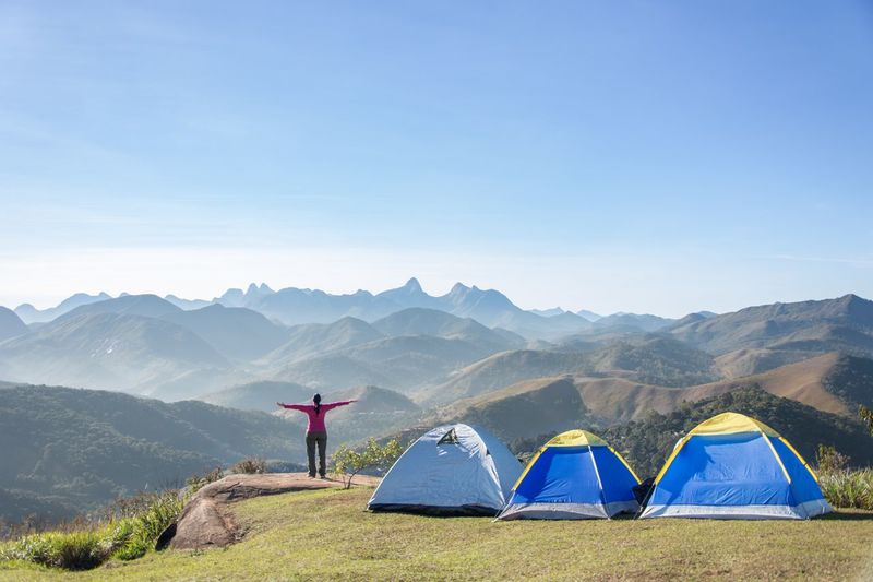 Woman Standing By Tents On Mountain Against Sky
