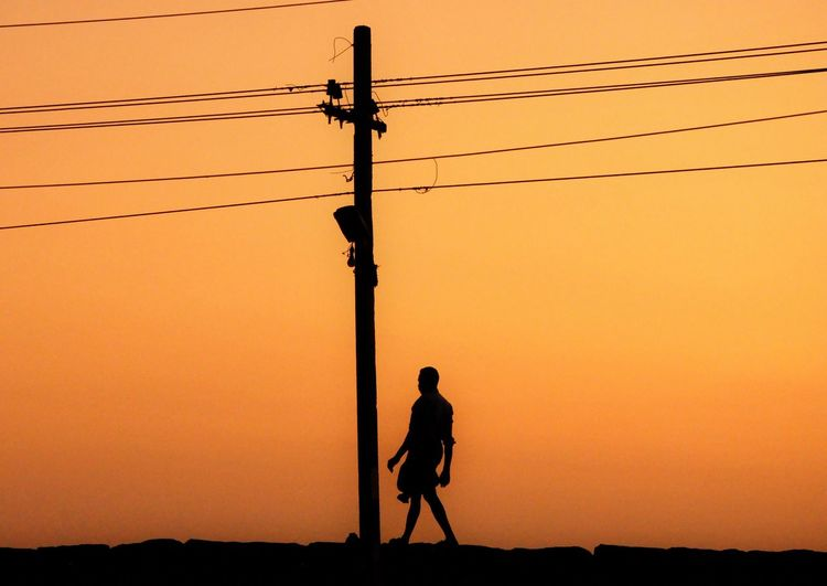 Silhouette man photographing electricity pylon against sky during sunset