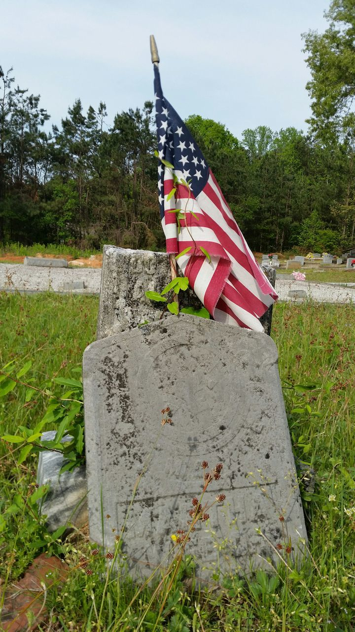 American Flag With Tombstone In Cemetery