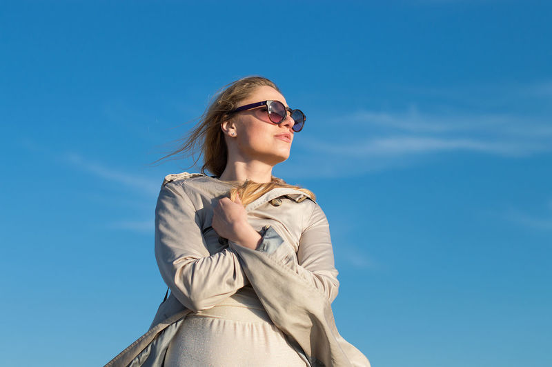 Low angle view of woman wearing sunglasses while standing against blue sky