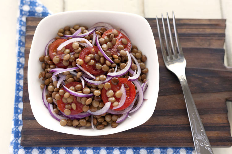 Fresh lentils, cherry tomatoes and spanish onion. Bowl on cutting board with fork. Natural Light Salad Spanish Onion Vegetarian Food Beauty In Nature Boiled Lentils Cherry Tomatoes Close-up Directly Above Food Food And Drink Freshness Healthy Eating Legume Salad Lentils No People Ready-to-eat Studio Photography Summer Salad Tomato Cherry Vegan Food