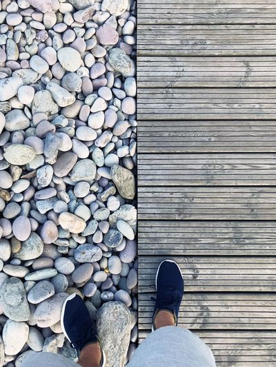 Low section of person standing on pebbles and boardwalk