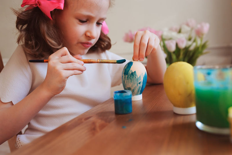 happy 7 years old kid girl painting easter eggs. Easter craft and holiday preparations at home. Colored Easter Fun Holiday Learning Paint Child Childhood Concentration Craft Day Egg Elementary Age Girls Home Interior Human Hand Indoors  Leisure Activity Lifestyles Preparation  Real People Sitting Table