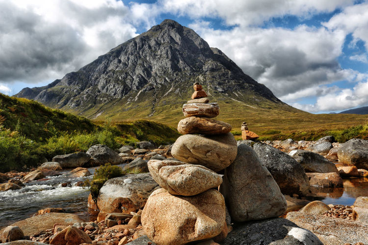 Stack of stones on rock against sky
