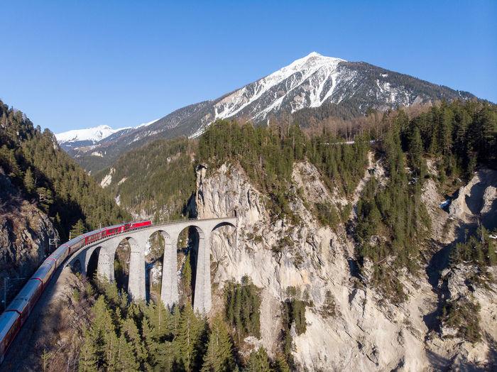 Panoramic shot of passenger train crossing landwasser viaduct in swiss alps