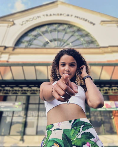 Portrait of young woman pointing while standing against building