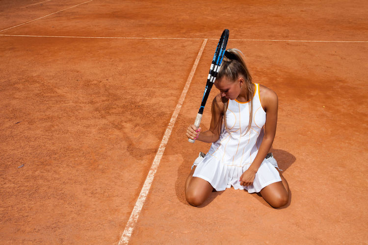 Woman with tennis racket sitting on court