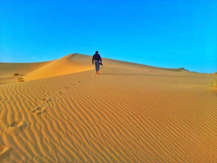 Walking on sand dunes on sahara desert of algeria