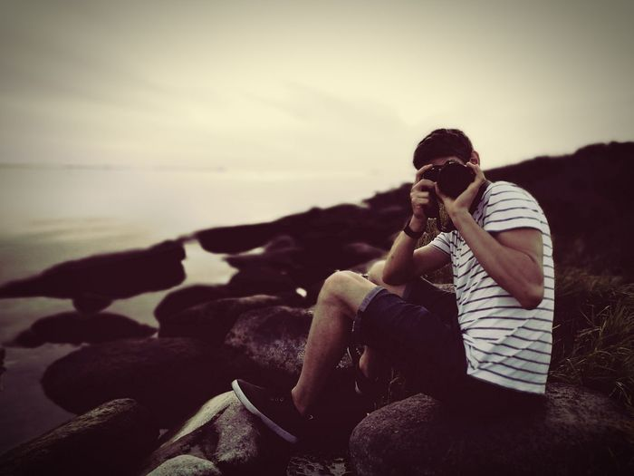 Man Photographing While Sitting On Rocks By Sea Against Sky
