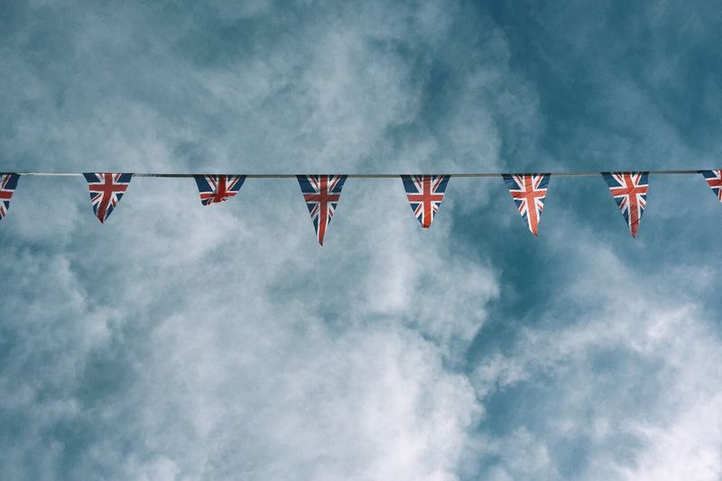 Low Angle View Of British Flags Bunting Against Cloudy Sky