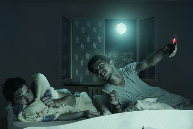Older brother laugh down the scared and sleepless boy at bedroom in front of shiny moon Bed Bedroom Brother Childhood Children Fear Horror Indoors  Laughing Leisure Activity Movıe Night Scare Scared Sleepless Watching