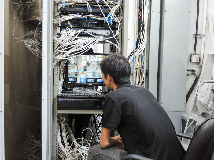 Rear view of man sitting in server room