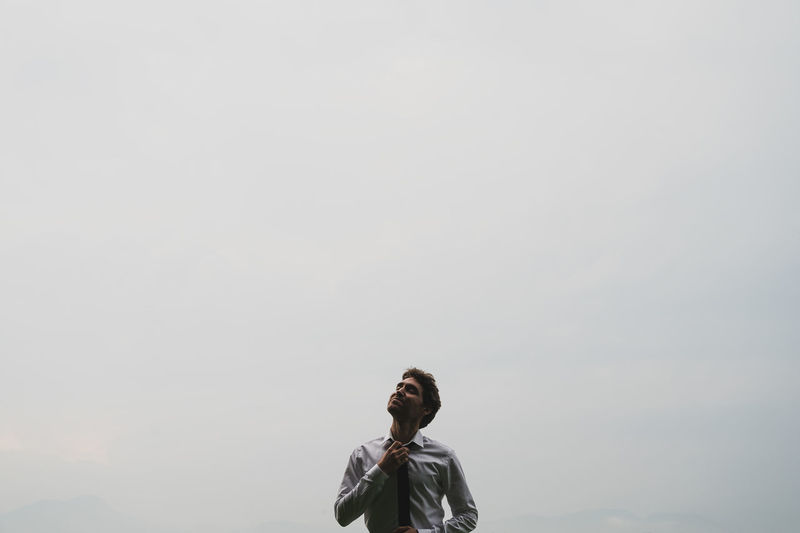 Mid adult man standing against sky