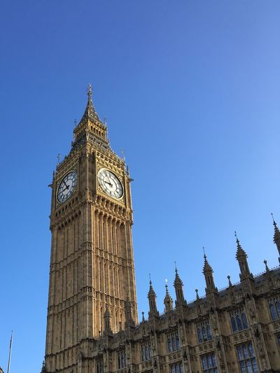 Low angle view of big ben against blue sky