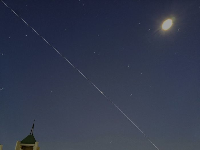 Low angle view of vapor trails in sky at night