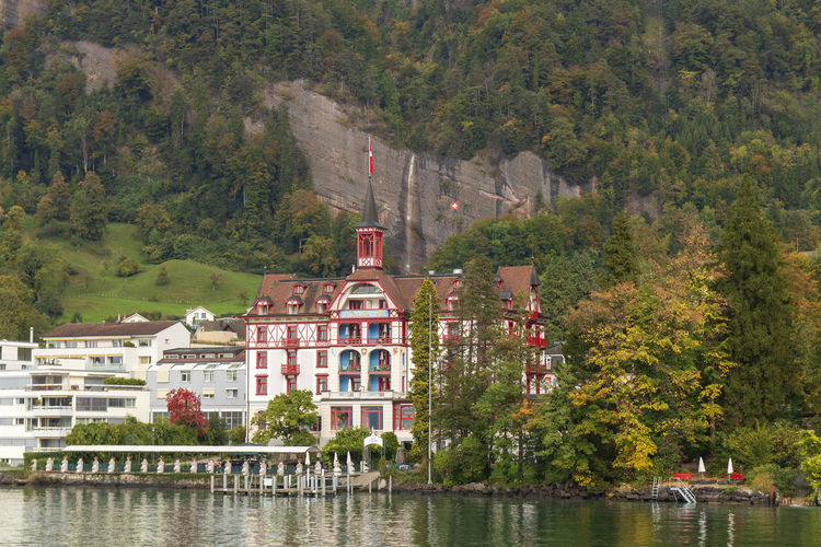 Houses by lake against trees and building