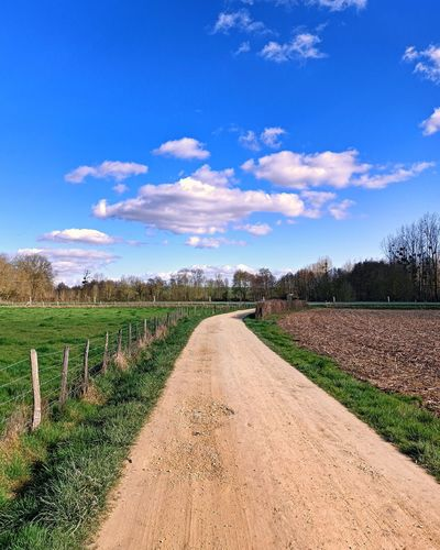 Road passing through agricultural field against sky