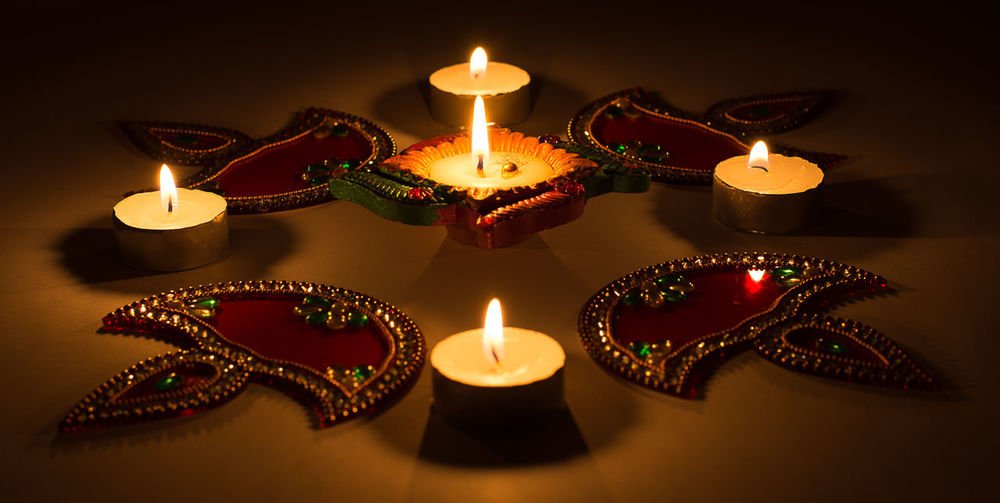 Close-Up Of Lit Diyas And Tea Light Candles On Table