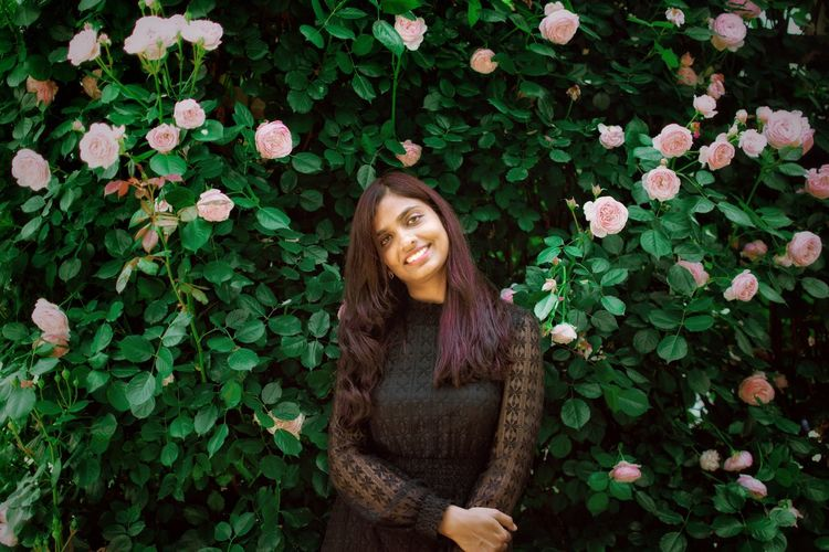 Portrait of a smiling young woman standing against british rose garden