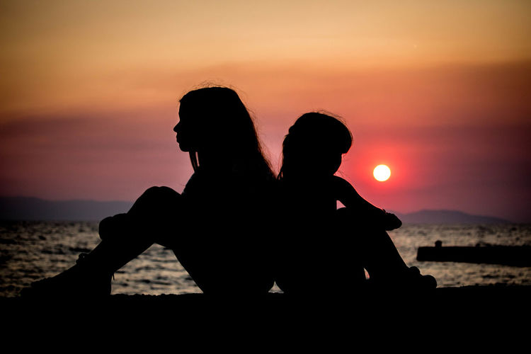 Silhouette sisters sitting on retaining wall against orange sky during sunset