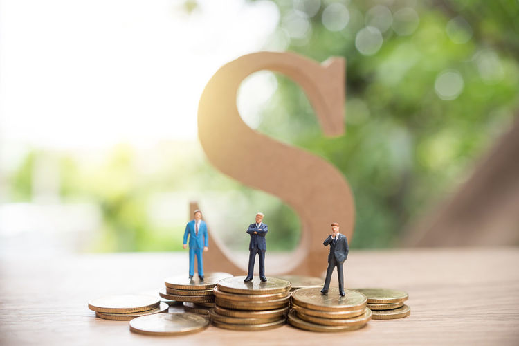 Figurines Standing On Coins