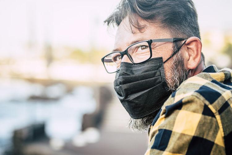 Close-up of man wearing mask sitting outdoors