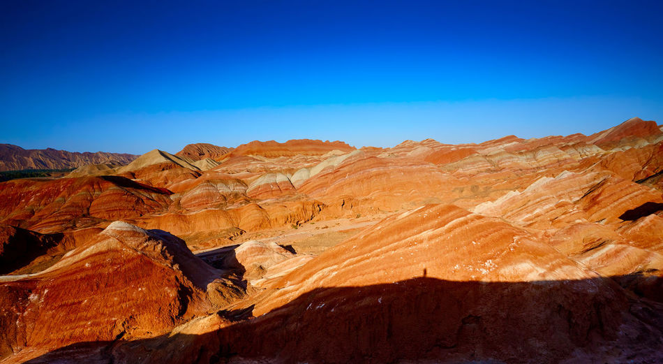 Zhangye colorful land in Gansu, China Beauty In Nature Blue Clear Sky Danxia Landform Day Desert Geology Landscape Mountain Nature No People Non-urban Scene Outdoors Physical Geography Rock - Object Rock Formation Scenics Sky Sunlight Sunset Tourism Tranquil Scene Tranquility Travel Destinations Zhangye