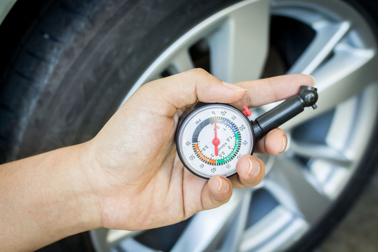 Cropped Hand Holding Pressure Gauge By Car Wheel