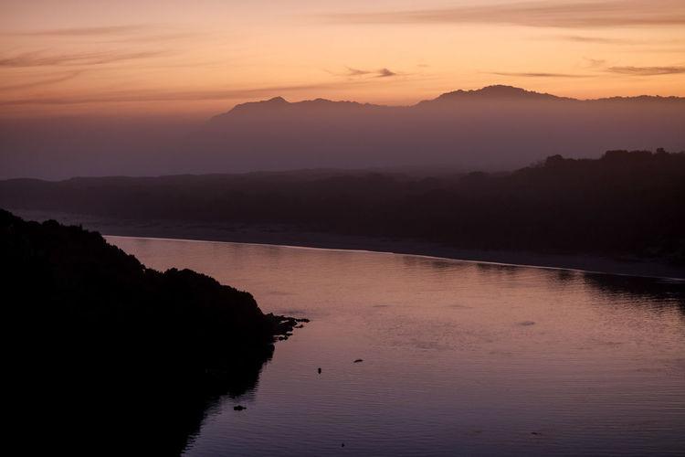 Calm lake along silhouette landscape