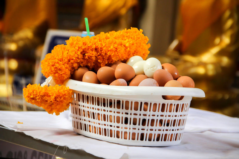 Eggs and marigold offering in basket