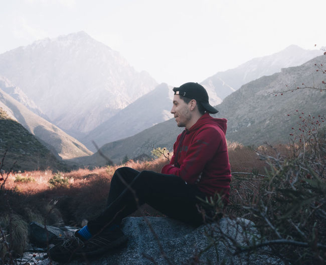 Side view of young man sitting on mountain