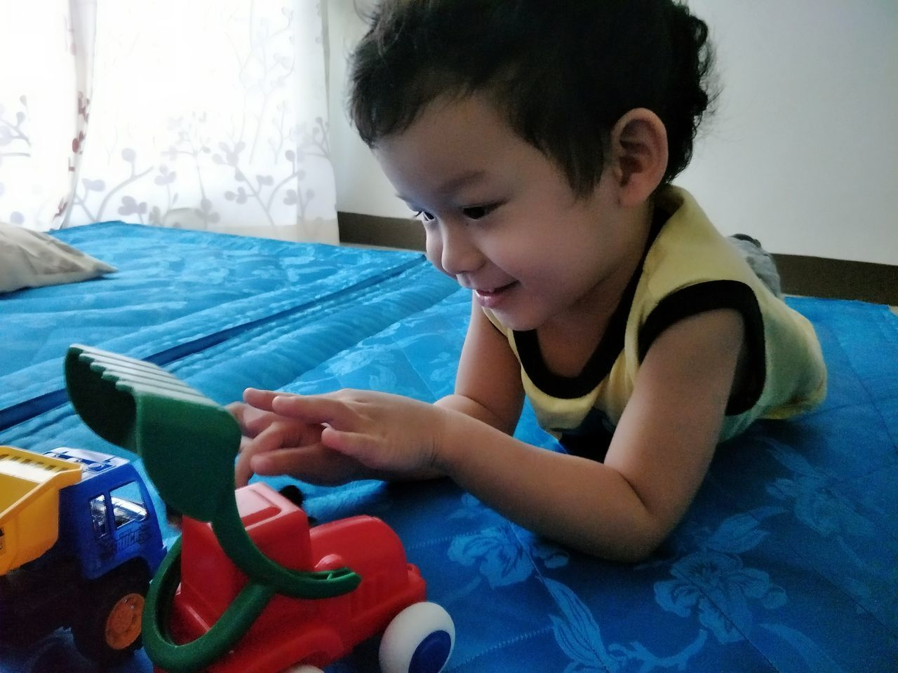 Smiling Boy Playing With Toy At Home
