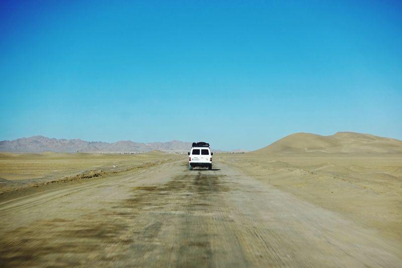 Car on desert land against clear blue sky