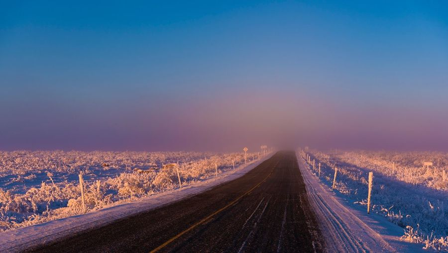 Road Amidst Landscape Against Clear Sky During Winter