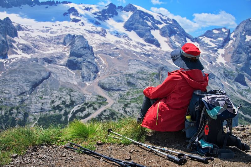 Senior woman sitting on mountain peak with beautiful view in background