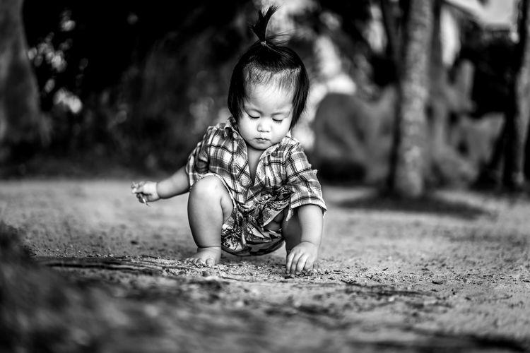 Cute boy playing in mud on field
