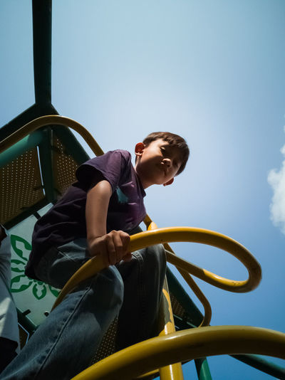 Low angle view of boy standing on play equipment