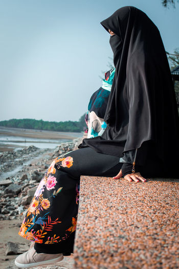 Side view of woman in burka sitting on retaining wall against sky